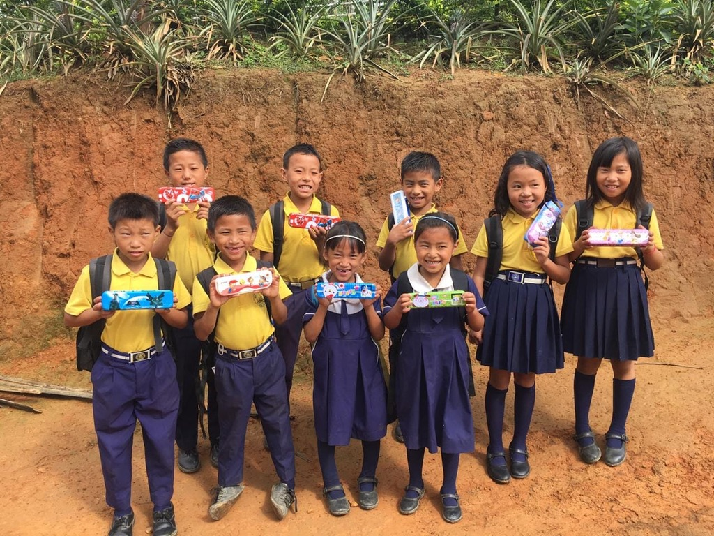 School children with end-of-term presents of pens and pencils