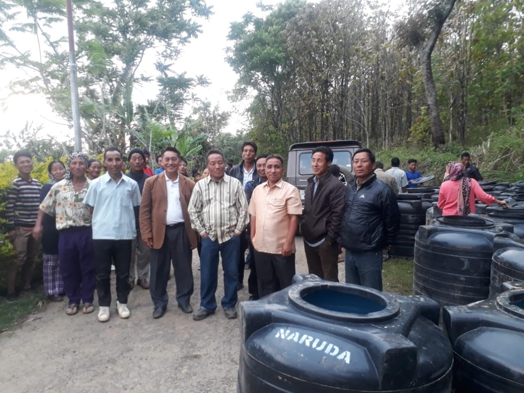 Village council members with 500L water tanks