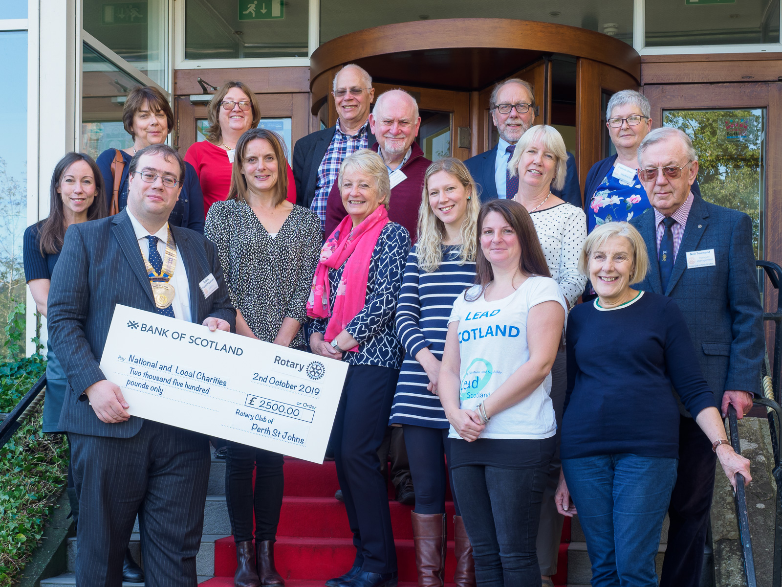 Charity representatives and Rotarians with a big cheque
