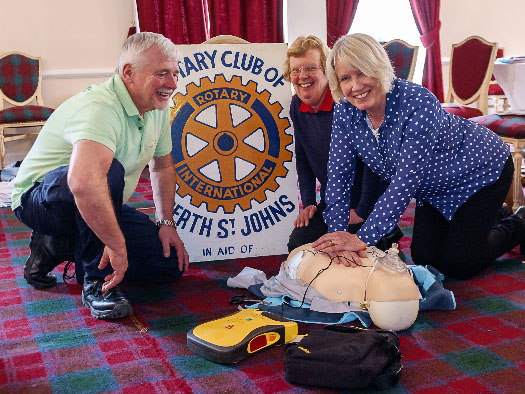 A club member practicing on a resuscitation dummy, with two others watching